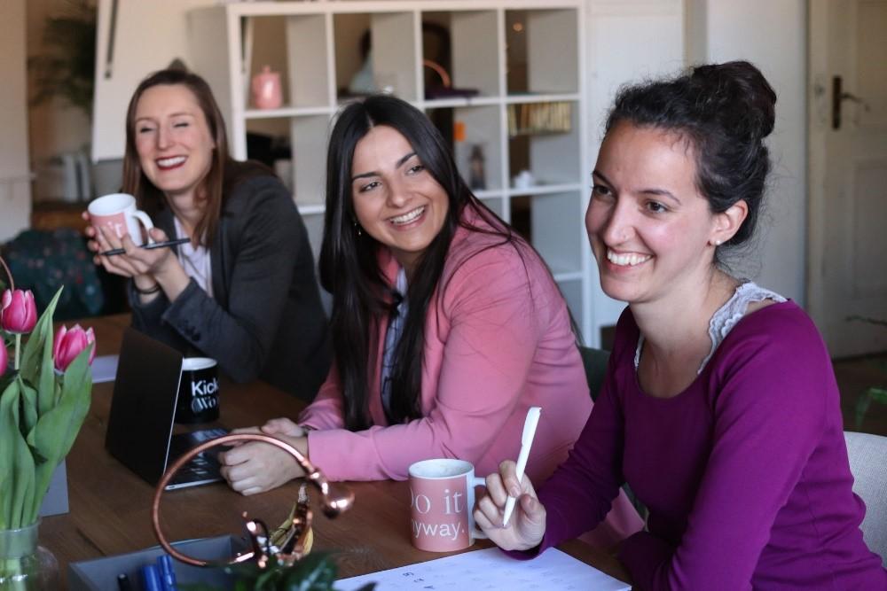 Kolme hymyilevää naista istuu kahvikuppien kanssa pöydän ääressä.